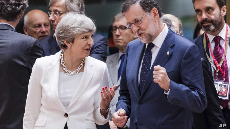 British Prime Minister Theresa May, center left, speaks with Spanish Prime Minister Mariano Rajoy, center right, as they arrive for a round table meeting at an EU Summit in Brussels, June 23, 2017.