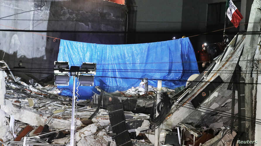 Members of rescue team place a blue tarp and a Mexican flag as they remove the last body trapped under rubble of a collapsed building at Alvaro Obregon Avenue in the Condesa neighborhood, after an earthquake in Mexico City, Mexico, Oct. 4, 2017.