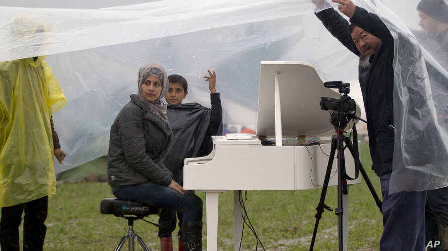 Syrian pianist Nour Alkhzam, center left, sits at the piano as Chinese dissident artist Ai Weiwei, right, holds a plastic sheet, during a heavy rain at the northern Greek border station of Idomeni, March 12, 2016.