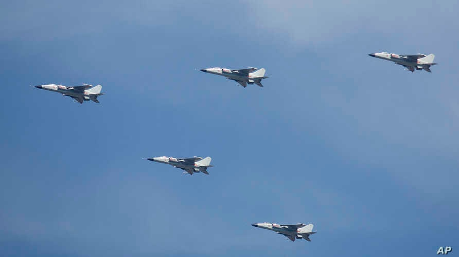 FILE Chinese JH-7 fighter-bombers fly in formation during a parade over Beijing, China, Sept. 3, 2015.