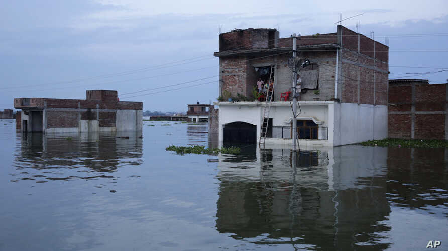 FILE - Indians watch from the upper floor of their house flooding in the river Ganges in Allahabad, India, Aug. 23, 2016.