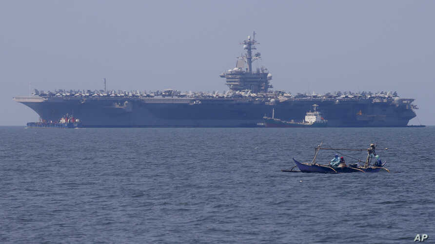 Fishermen on board a small boat pass by the USS Carl Vinson aircraft carrier at anchor off Manila, Philippines, Feb. 17, 2018.