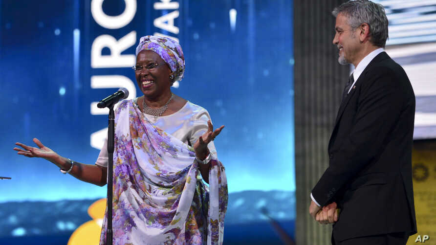 US Actor George Clooney, right, listens to Marguerite Barankitse, after presenting her the first Aurora Prize, an award recognizing an individual's work to advance humanitarian causes during an awarding ceremony in Yerevan, Armenia, Sunday, April 24,