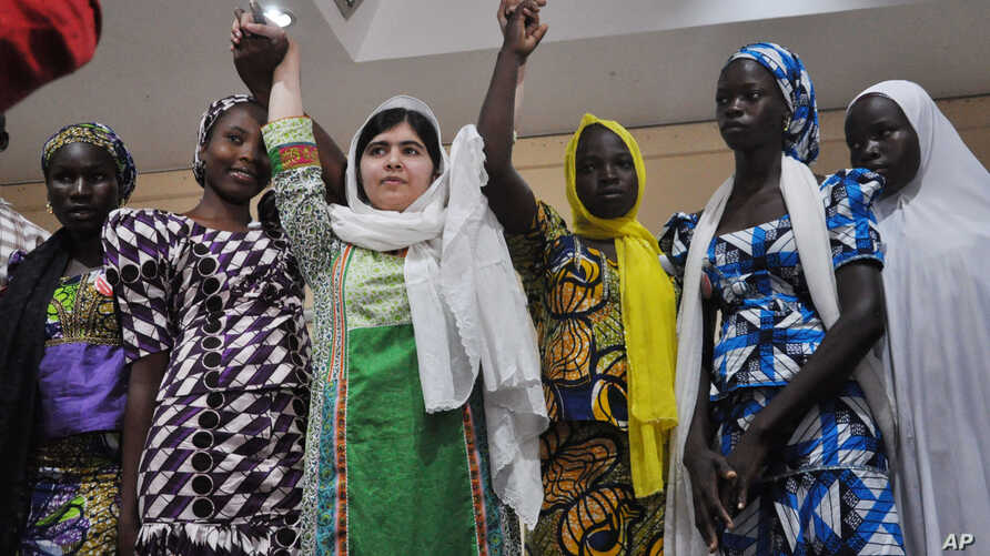 Pakistani activist Malala Yousafzai, center, was named a winner of the Nobel Peace Prize. She's shown with escaped kidnapped school girls from Chibok  in Abuja, Nigeria, July 14, 2014.