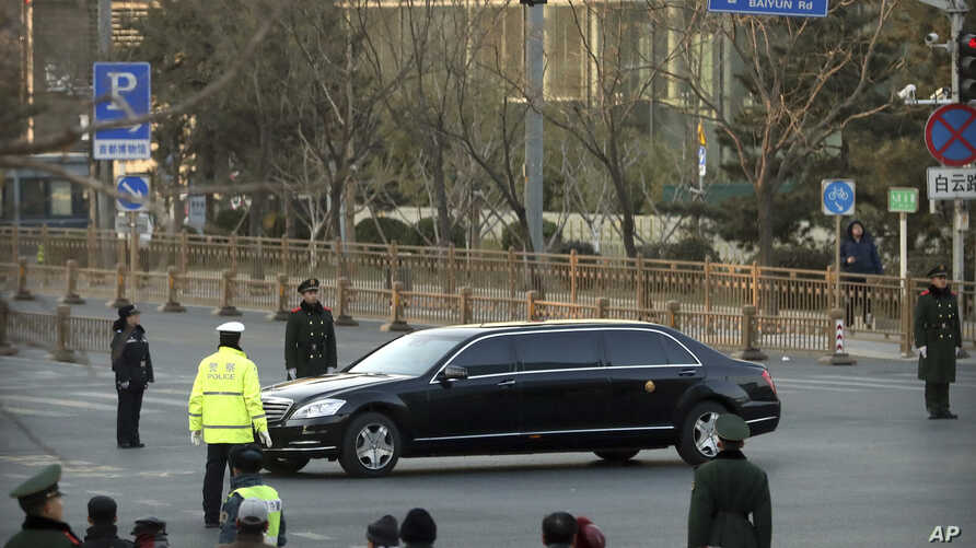 Security officials stand guard while a Mercedes limousine in a motorcade believed to be carrying North Korean leader Kim Jong Un passes along a street in Beijing, Wednesday, Jan. 9, 2019.