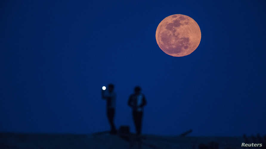 A man takes a picture of the moon rising during a lunar eclipse, in a suburb of Shanghai, April 15, 2014.