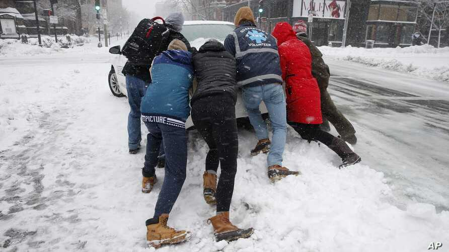 People push a stranded taxi during a snowstorm, Tuesday, March 13, 2018, in Boston.  The third major nor'easter in two weeks slammed New England on Tuesday, bringing blizzard conditions and more than a foot of snow to some communities.