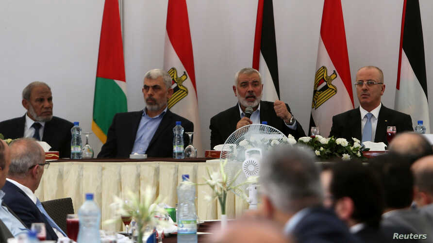 Hamas Chief Ismail Haniyeh speaks as he sits next to Palestinian Prime Minister Rami Hamdallah during the meeting in Gaza City, Oct. 3, 2017.
