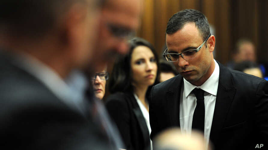 Oscar Pistorius (r) followed by his sister Aimee, leaves court in Pretoria, South Africa, March 28, 2014, after the trial was postponed after one of the legal experts who will assist the judge in reaching a verdict is sick.