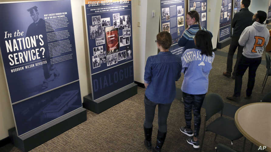 """Princeton University students walk through an exhibit titled, """"In the Nation's Service? Woodrow Wilson Revisited,"""" April 3, 2016, at the Woodrow Wilson School of Public and International Affairs in Princeton, New Jersey."""