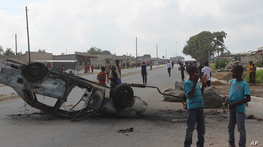 FILE - A burnt out vehicle lays on it's roof in Lusaka, Zambia, April 7, 2016. On Wednesday police arrested more than 250 people for alledgedly attacking Rwandan nationals and looting their stores in violence that police said killed two people in rit