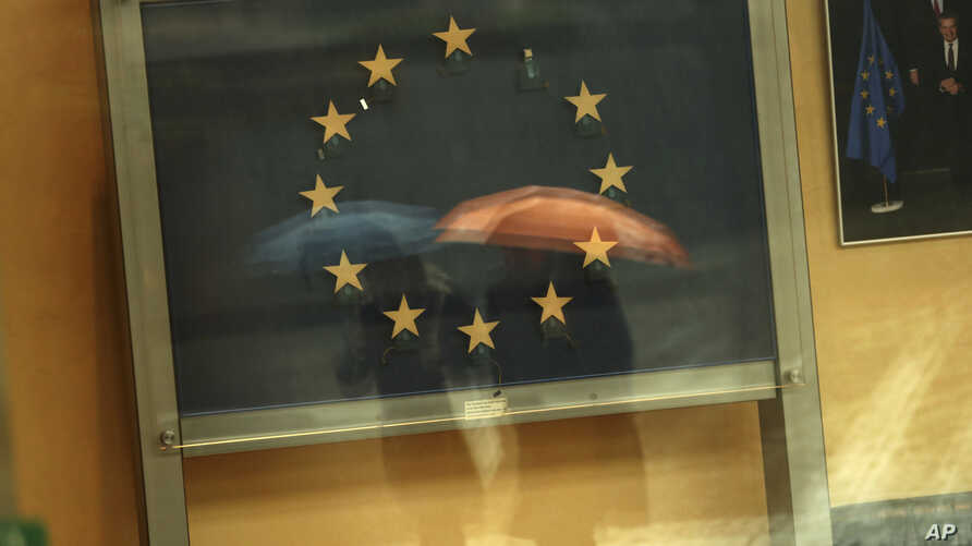 Passers-by are reflected in an artwork based on the European Union flag, with one star missing, in the European Commissions headquarters in Brussels, Nov. 12, 2018.
