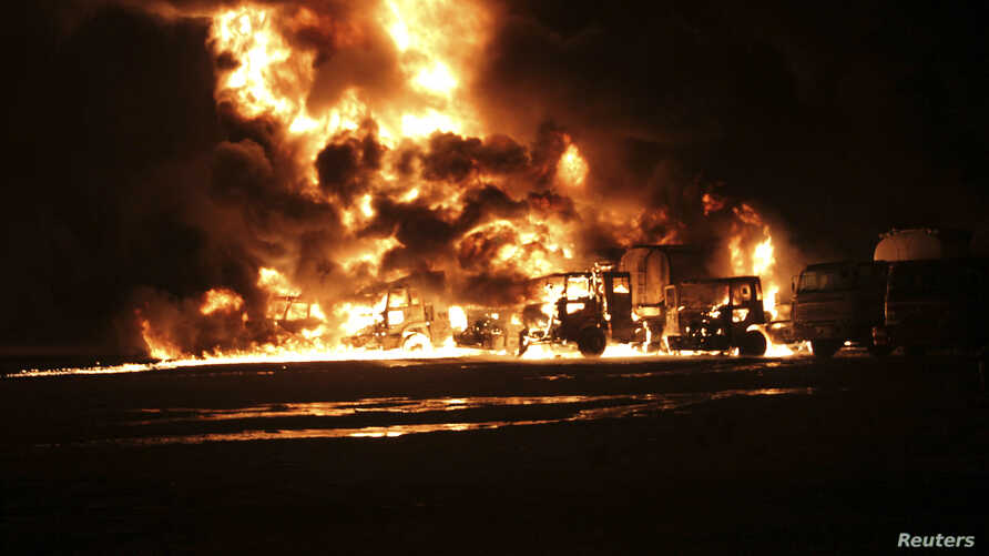 A NATO supply convoy burns after it was attacked in Hub, near Karachi, Pakistan, Sept. 15, 2013.