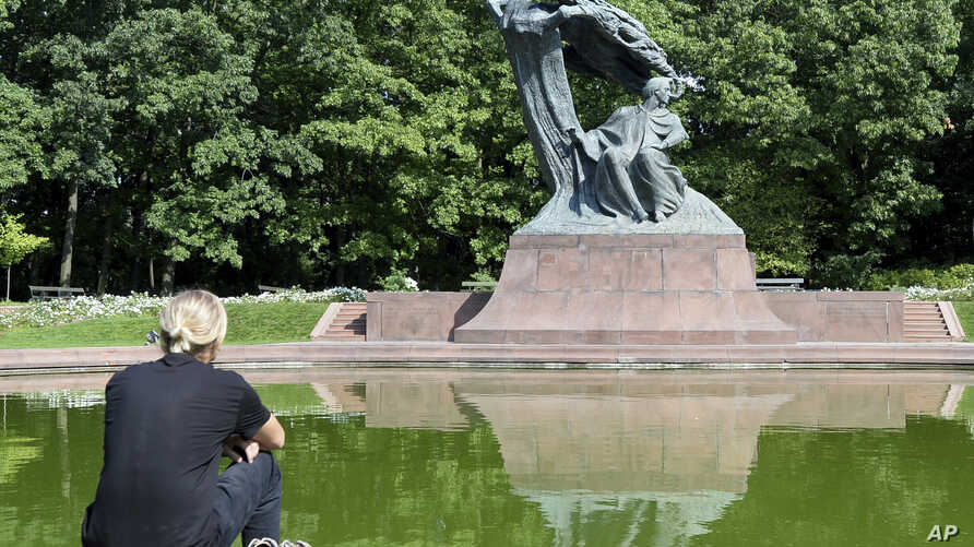 A tourist sits by the Chopin monument in Lazienki park in Warsaw, Poland, Sept. 3, 2018.