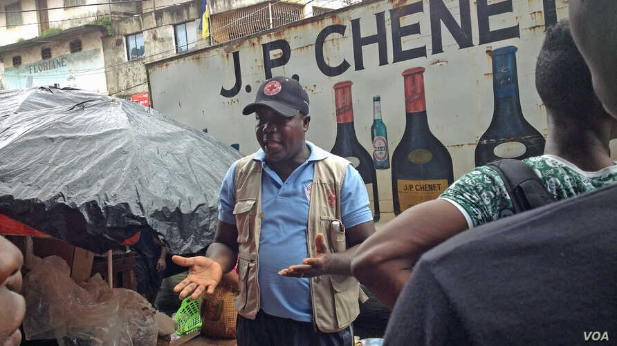 Joseph Garber talks to people in the east part of Freetown about Ebola prevention. July 28, 2015 (N. deVries/VOA)