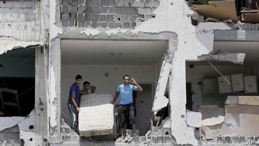 Mideast Israel PalestiniansPalestinians salvage what they can of their belongings from the rubble of their destroyed apartment in a building hit by an Israeli strike in Beit Lahiya, northern Gaza Strip, Aug. 4, 2014.