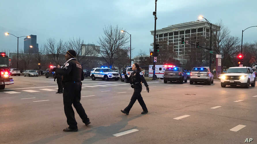 Chicago police officers walk outside Mercy Hospital on the city's South Side where authorities say a shooting at the hospital has wounded multiple people, including a suspect and a police officer, Nov. 19, 2018.