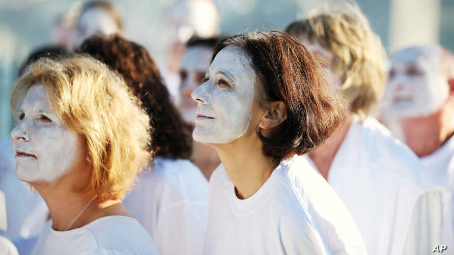 FILE - Demonstrators from the environmental group Greenpeace paint their faces white to highlight coral bleaching in Sydney, Friday, April 22, 2016.