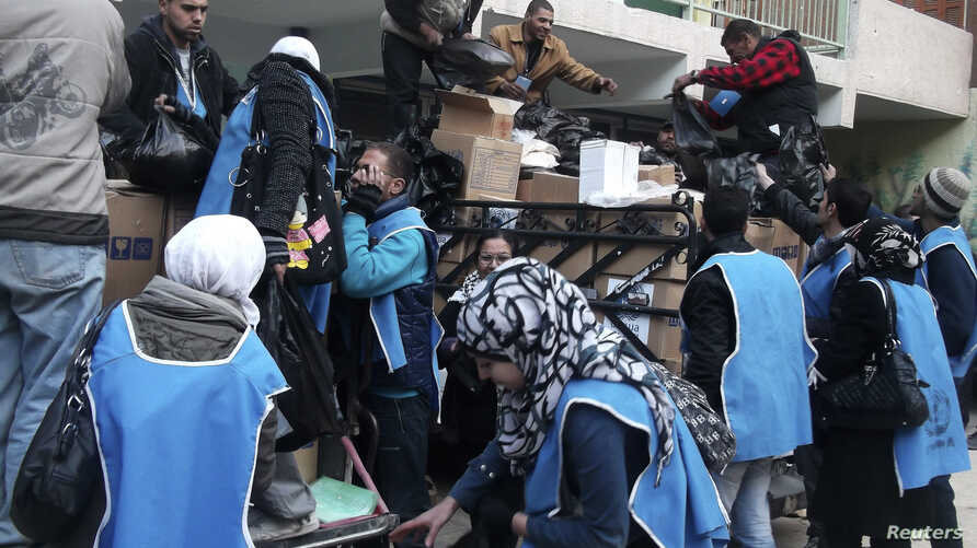 U.N. Relief and Works Agency (UNRWA) workers prepare aid parcels at the Palestinian refugee camp of Yarmouk, south of Damascus in this picture made available on February 26, 2014. World powers have passed a landmark Security Council resolution demand