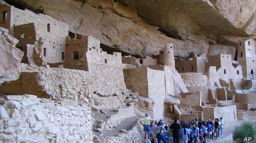 FILE - In this Aug. 27, 2005 photo, visitors tour Cliff Palace, an ancient cliff dwelling in Mesa Verde National Park, Colorado.