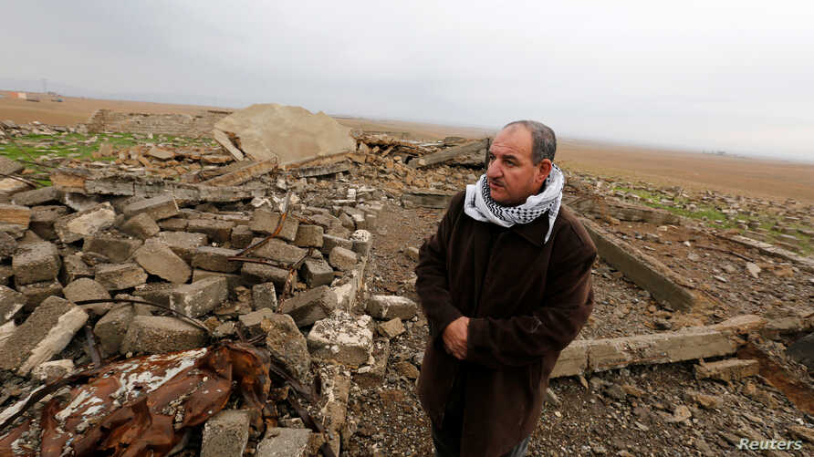 FILE - Farmer Sami Yuhanna inspects his farm and the buildings destroyed by clashes in Qaraqosh, Iraq, Feb. 9, 2017. To help the country's farmers to restart or expand, the UN food agency said it would distribute cash securely via mobile phone.