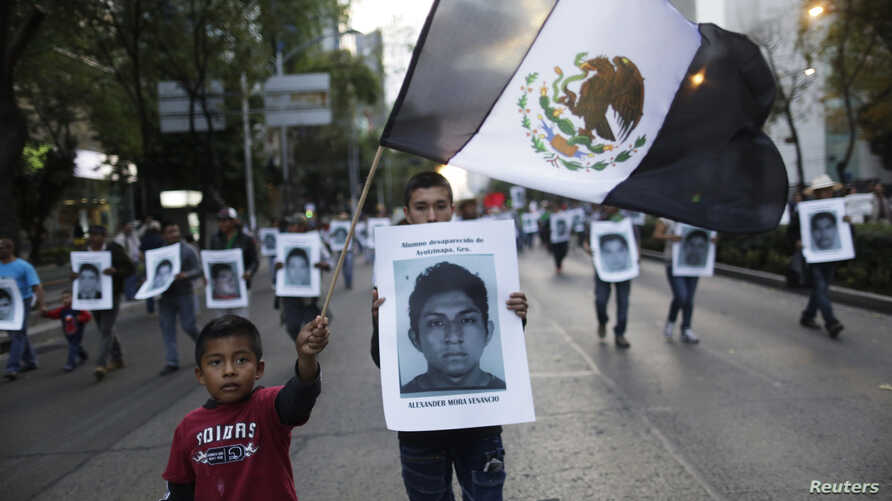Demonstrators carry photos of the 43 missing trainee teachers as a boy waves a Mexican flag, with its green and red parts replaced with black as a sign of mourning, during a march in support of  the students in Mexico City, Dec. 6, 2014.