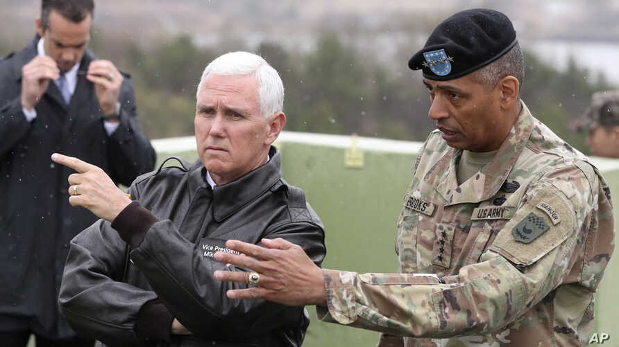 U.S. Vice President Mike Pence, left, is briefed by U.S. Gen. Vincent Brooks, right, commander of the United Nations Command, U.S. Forces Korea and Combined Forces Command from Observation Post Ouellette in the Demilitarized Zone (DMZ), near the bord...