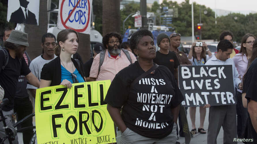 "Protestors carry signs during a demonstration by ""Black Lives Matter"" in Los Angeles, California August 11, 2015."