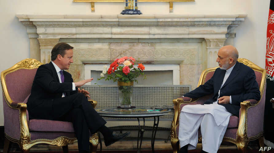 Britains' Prime Minister David Cameron (L) gestures during a meeting with Afghan President Hamid Karzai (R) at The Presidential Palace in Kabul on July 19, 2012. British Prime Minister David Cameron held talks in the Afghan capital with President Ham