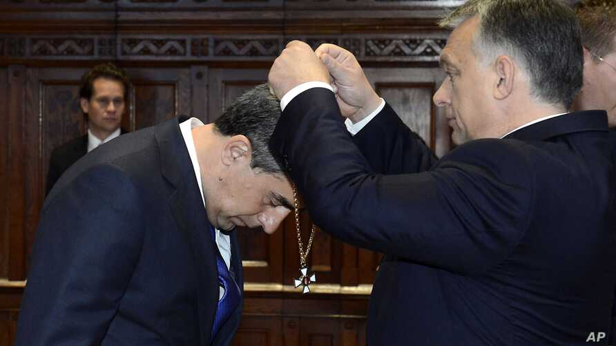 FILE - Bulgarian President Rosen Plevneliev, left, is awarded with the Grand Cross of the Hungarian Order of Merit with Chain and Star with Golden Beams by Hungarian Prime Minister Viktor Orban in the Parliament building in Budapest, Hungary, Thursda