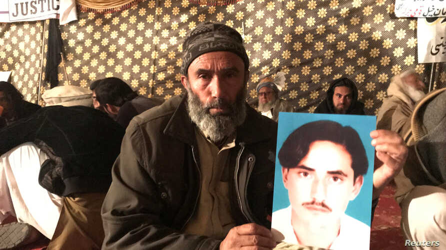 """FILE - Mohammad Bilal holds a picture of his son Hazratullah as he takes part in a protest with members of the Pashtun community against what they say are enforced """"disappearances"""" and routine oppression, in Islamabad, Feb. 8, 2018."""