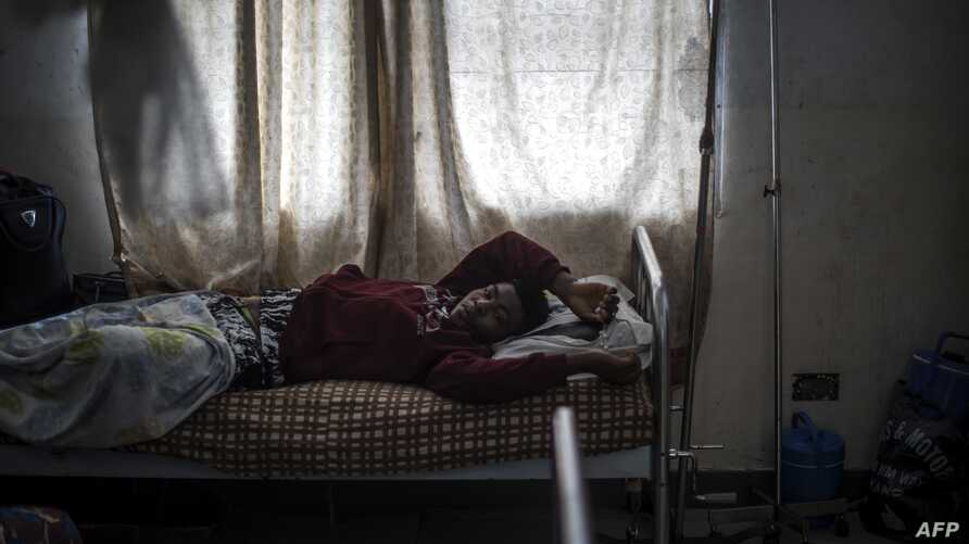 Mbuh Ronaldo, 20, clings to a rosary as he lies in a hospital bed in Buea, the capital of Cameroon's majority English-speaking southwest region, Oct. 4, 2018.