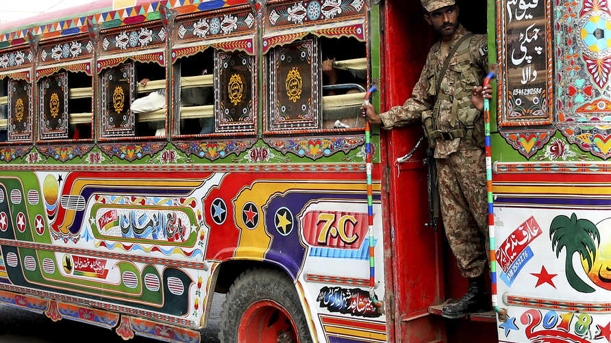 A Pakistani soldier stands guard in a bus carrying election staff and polling related material to stations in Karachi, Pakistan, July 24, 2018.