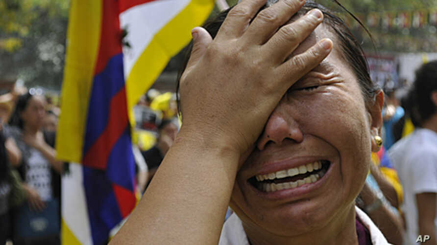An exiled Tibetan woman cries after Jampa Yeshi, a Tibetan self immolated during a protest,  in New Delhi, India ( File- March 26, 2012.)