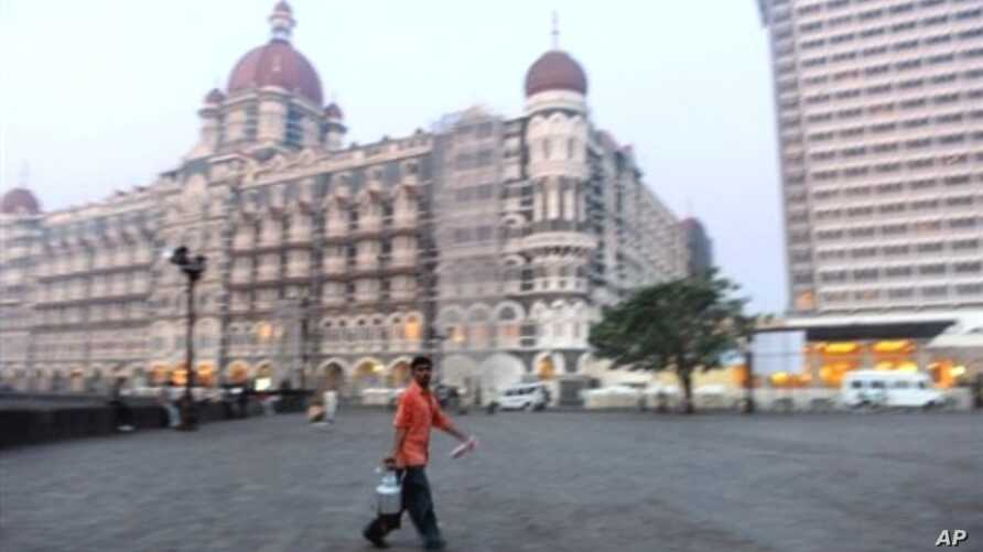 A tea vendor strolls across the popular Gateway of India monument plaza, opposite the landmark Taj Mahal hotel which was attacked by militants in November 2008 (file photo)
