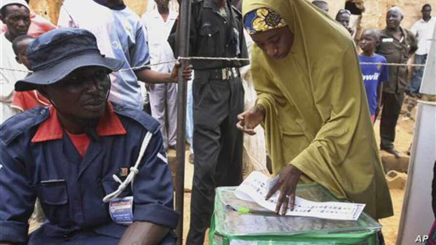 A Muslim woman prepares to vote during a gubernatorial election in Kaduna, Nigeria, Thursday, April 28, 2011. Two states in Nigeria's Muslim north voted Thursday for state gubernatorial candidates after their polls were delayed by violence that kille