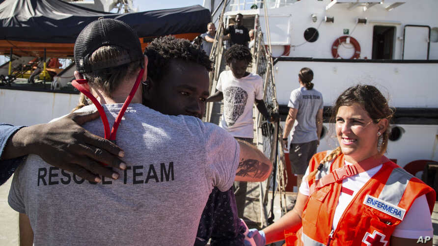 In this photo taken Thursday, Aug. 9, 2018, migrants disembark from the the Open Arms boat, in Algeciras, Spain, after being rescued off the coast of Libya in the early hours of the nigh of Thursday, Aug. 2, 2018.