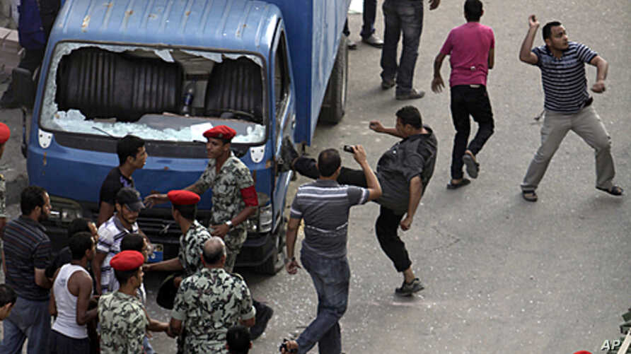 Protesters kick a police car, smash the windows and throw stones at the court complex in Suez, about 110km (68 miles) northeast of Cairo, Egypt, July 6, 2011