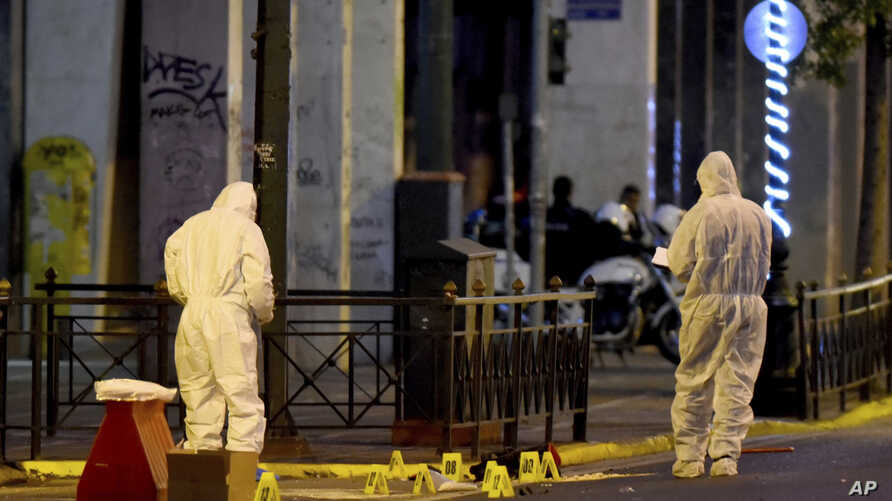 Members of the bomb squad search for evidence outside Labor Ministry in Athens, Dec. 12, 2016.