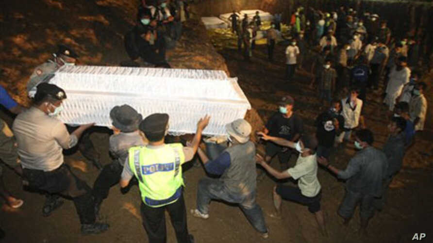 Indonesian volunteers and police carry a coffin at a mass burial site of the victims of the Mount Merapi volcano eruption, 7 November 2010