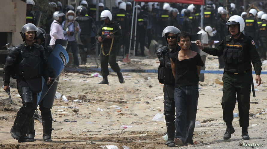 A protester is detained during clashes between garment workers and security forces in Phnom Penh a year ago, on January 3, 2014.