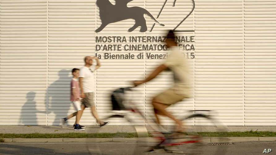 People pass by the logo of the 72nd edition of the Venice Film Festival, at the Venice Lido, Aug. 31, 2015.