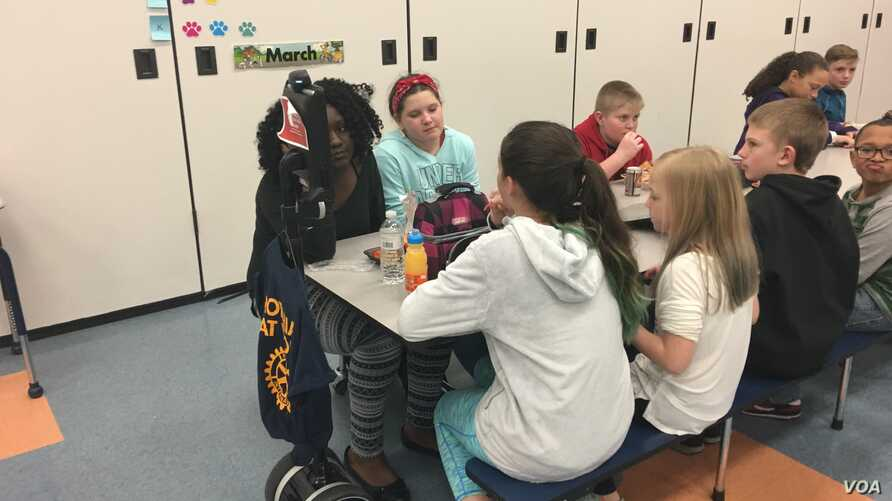 """Cloe Gray goes to lunch with her classmates — virtually — at Point Pleasant Elementary School in Glen Burnie, Maryland. That's """"Clo-Bot"""" at the head of the table. (E. Cherneff/VOA)"""