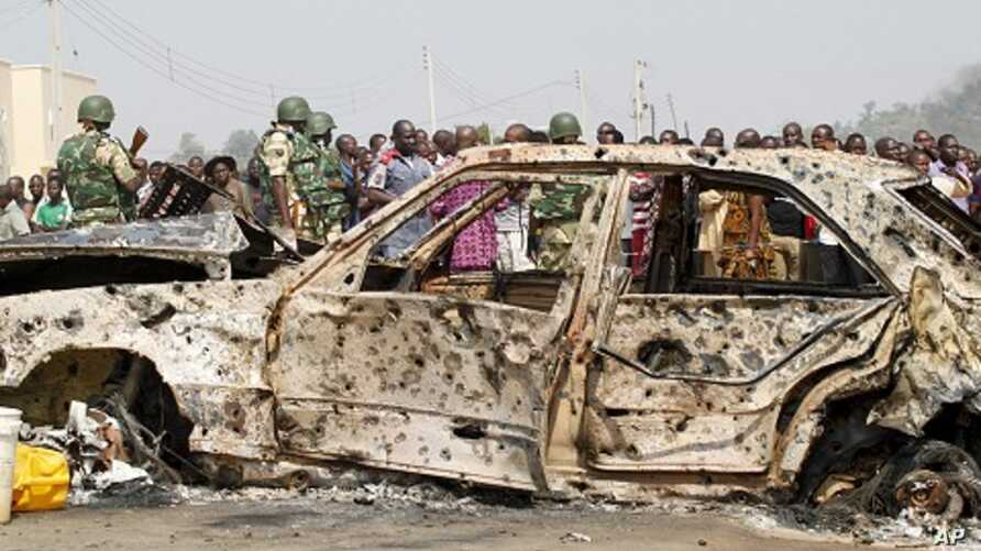 A crowd gathers near a car damaged by an explosion at St. Theresa Catholic Church at Madalla, Suleja, just outside Nigeria's capital Abuja, December 25, 2011.