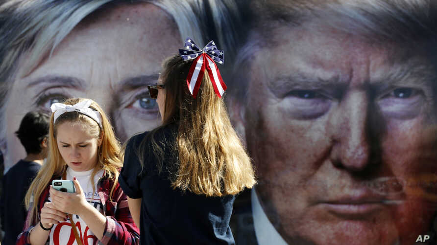 FILE - Girls pause near a bus displaying large photos of candidates Hillary Clinton and Donald Trump before the presidential debate at Hofstra University in Hempstead, New York, Sept. 26, 2016.