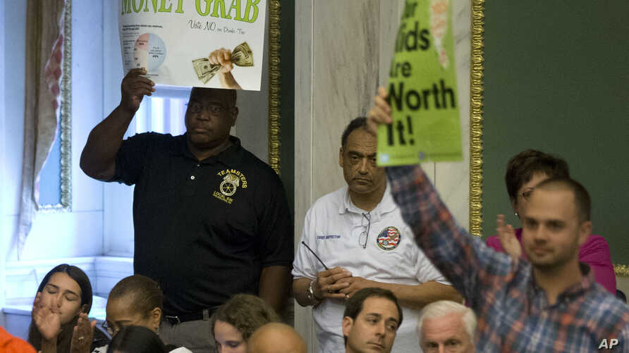 Audience members react after the Philadelphia City Council passed a tax on sugary and diet beverages, in Philadelphia, June 16, 2016.