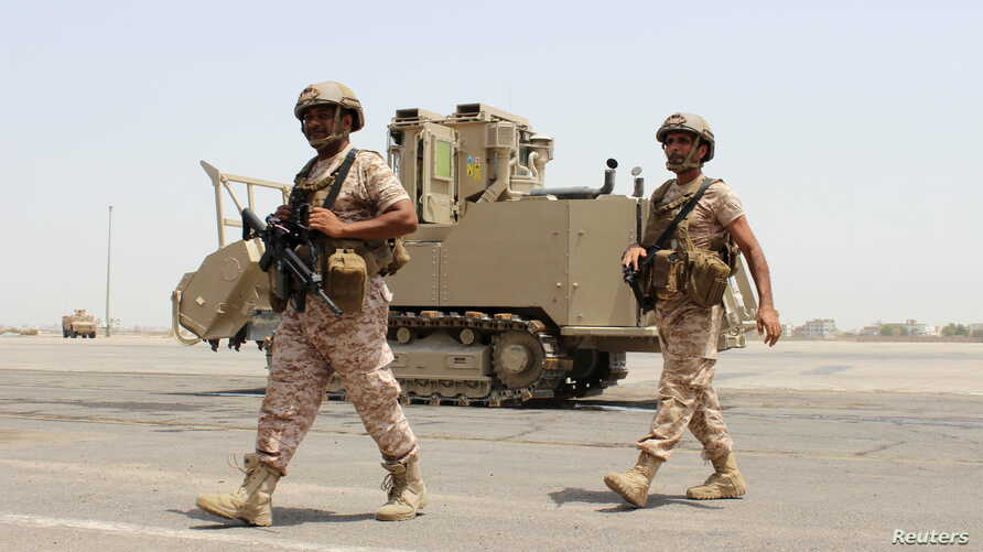 Soldiers from the United Arab Emirates walk past a military vehicle at the airport of Yemen's southern port city of Aden, Aug. 12, 2015.