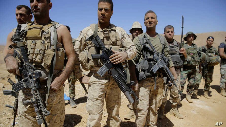 FILE - Lebanese soldiers listen to a briefing from an official during a media trip organized by the Lebanese army on the outskirts of Ras Baalbek, northeast Lebanon, Aug. 28, 2017.