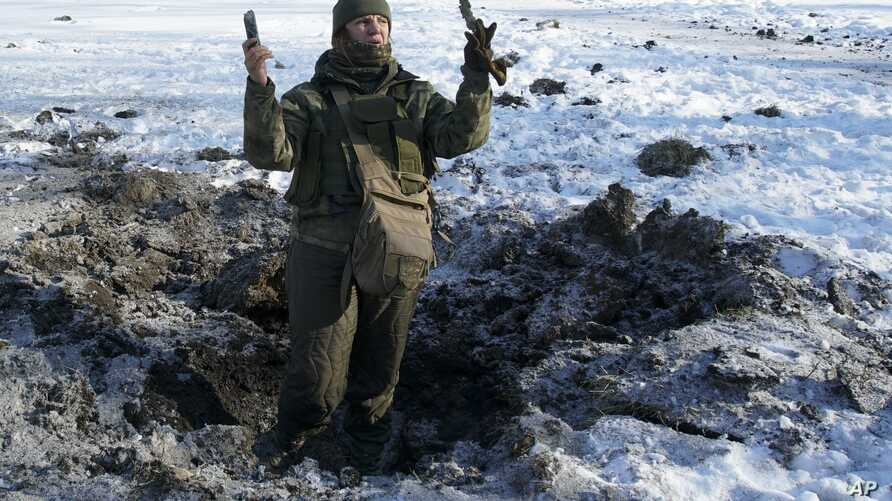 A Ukrainian soldier shows pieces of shrapnel in a crater left by an explosion in Avdiivka, Ukraine, Jan. 31, 2017.