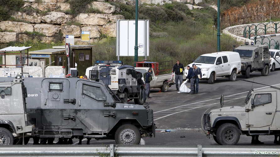 Israeli security forces inspect the scene of what the Israeli military said were back-to-back gun and car-ramming attacks by Palestinians, near the Jewish settlement of Kiryat Arba near the West Bank city of Hebron, March 14, 2016.